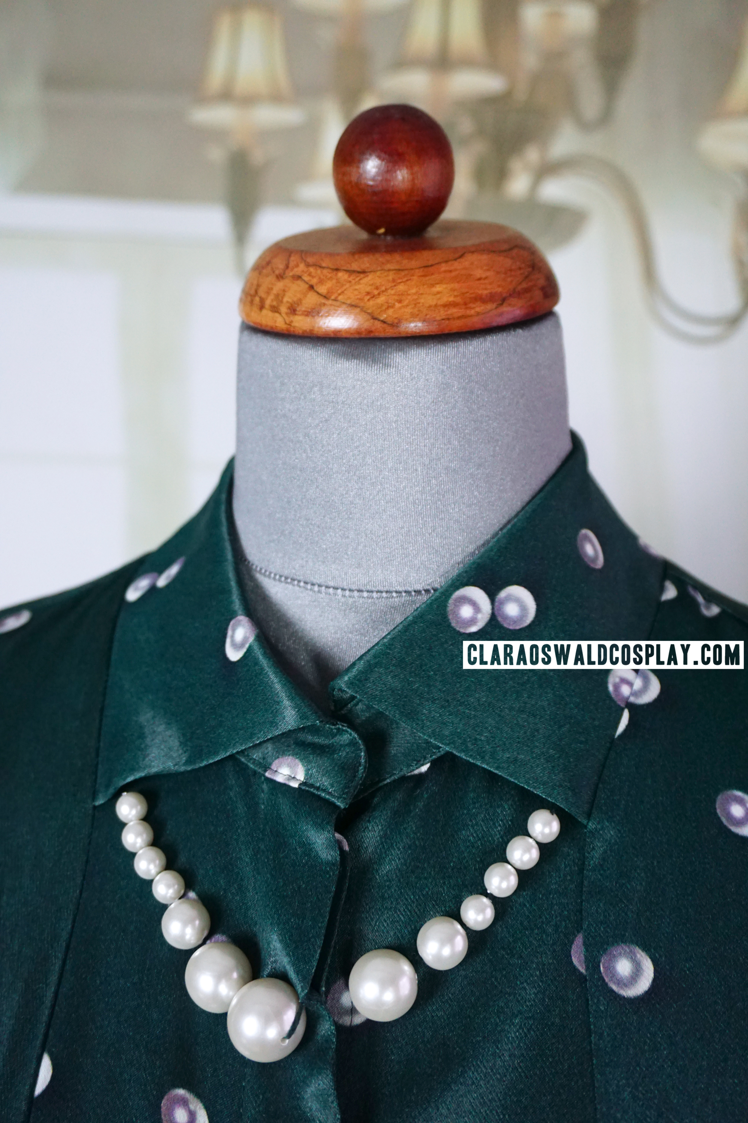 The pearls around the collar are actual not part of the print but sewn on. They were likely taken off by the costume department
