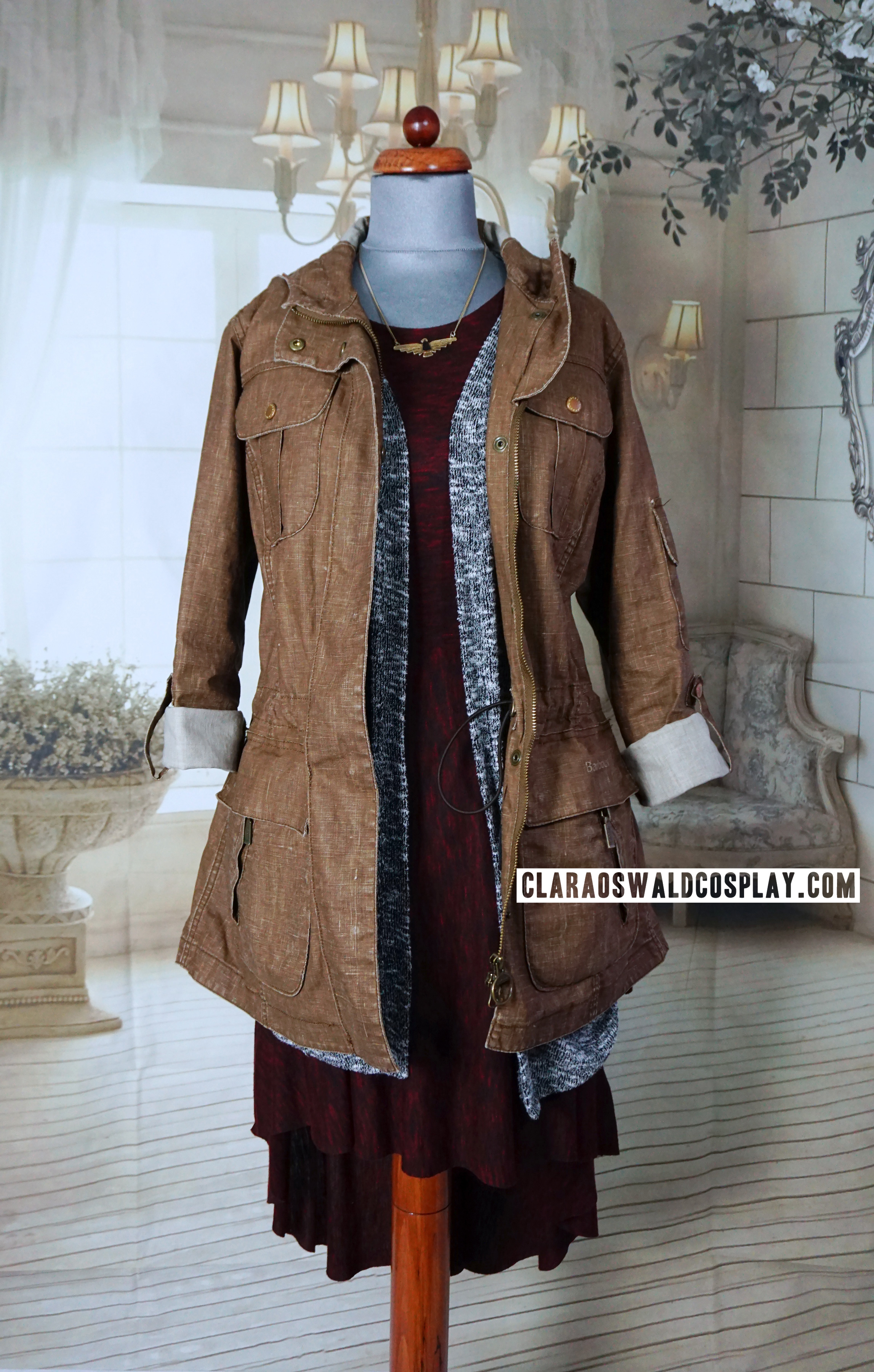Clara Oswald's Bells of Saint John outfit featuring the Urban Outfitters Silence + Noise Space Dye Fishtail Dress, Urban Outfitters Sparkle & Fade Cardigan in grey, Barbour Vintage Duralinen Force Parka (Sandstone colour alt) and Urban Outfitters Aztec Eagle Necklace